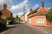 Traditional old buildings line the road at the village of Hollesley, Suffolk, England