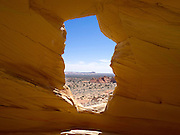 "Sandstone Window near Melody Arch, in the vicinity of North Coyote Buttes area known as ""The Wave,"" Vermillion Cliffs National Monument, Arizona, known for its beautiful rock formations. The area known as White Pocket is in the distance."