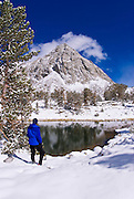 Hiker on the shore of lower Gem Lake in winter, John Muir Wilderness, Sierra Nevada Mountains, California