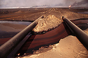 A small river of oil flows through the desert in the burning northern Al-Rawdhatain oil fields in Kuwait after the end of the Gulf War in May of 1991. More than 700 wells were set ablaze by retreating Iraqi troops creating the largest man-made environmental disaster in history.