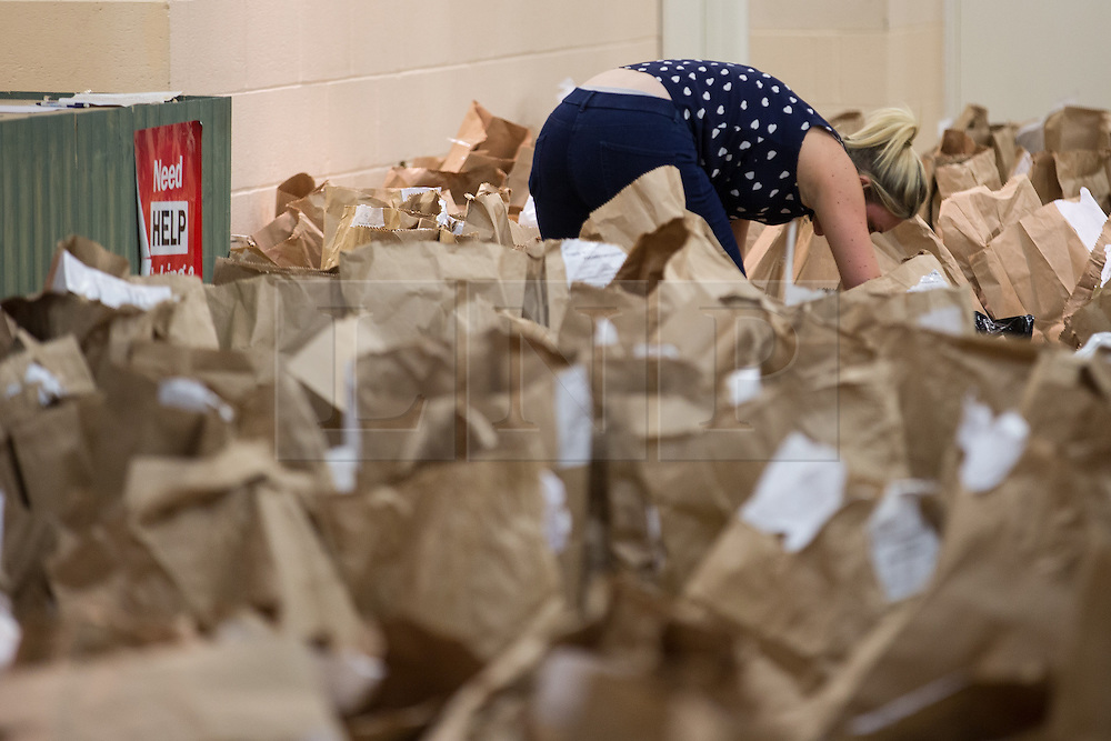 © Licensed to London News Pictures . 07/05/2015 . Doncaster , UK . A woman searches through dozens of bags of unused ballets in a side room , next to the count . The count for the 2015 General Election in Labour Party leader Ed Miliband's constituency of Doncaster North , at Doncaster Racecourse . Photo credit : Joel Goodman/LNP