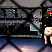 A trainer and his pupil practice some punching techniques inside an octagon at West Coast Jiu Jitsu in Oxnard, Calif., on August 27, 2007. Mixed Martial Arts is a sport practiced by people of all ages.