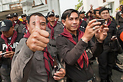 "Mar. 27, 2010 - BANGKOK, THAILAND:  Thai police officers, who are supposed to control the Red Shirts protests, applaud, photograph and cheer for the Red Shirts as they march through Bangkok Saturday, March 27. More than 80,000 members of the United Front of Democracy Against Dictatorship (UDD), also known as the ""Red Shirts"" and their supporters marched through central Bangkok March 27 during a series of protests against and demand the resignation of current Thai Prime Minister Abhisit Vejjajiva and his government. The protest is a continuation of protests the Red Shirts have been holding across Thailand. They support former Prime Minister Thaksin Shinawatra, who was deposed in a coup in 2006 and went into exile rather than go to prison after being convicted on corruption charges. Thaksin is still enormously popular in rural Thailand.    PHOTO BY JACK KURTZ"