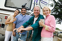 Two middle-aged couples standing beside caravan