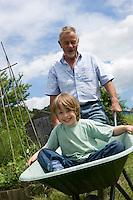 Grandfather pushing boy in wheel barrow