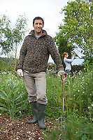 Man with spade standing in garden portrait