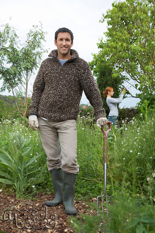 Man with spade standing in garden portrait