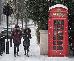 © Licensed to London News Pictures. 02/03/2018. London, UK. A couple walk past a red phone box as further snowfall covers the landscape in Little Venice, Westminster, London. The 'Beast from the East' and Storm Emma have brought extreme cold, ice and heavy snow to the UK. Photo credit: Ben Cawthra/LNP