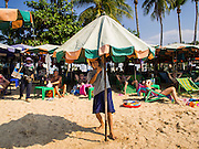 06 JANUARY 2015 - PATTAYA, CHONBURI, THAILAND:  A beach umbrella vendor opens an umbrella on Pattaya beach. The Thai government has announced plans to clean up Pattaya beach, one of the most famous beaches in Thailand. Pattaya is about 2.5 hours from Bangkok. They plan to reduce the number of umbrella and chaise lounge vendors on the beach and regulate the personal watercraft and parasailing vendors on the beach. The government has already cleaned up beaches on Phuket island and Hua Hin.   PHOTO BY JACK KURTZ