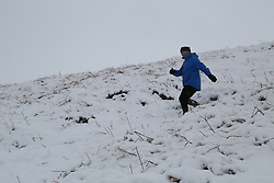 © Licensed to London News Pictures.04/03/16. Ilkley, UK. A man clambers through the deep snow on Ilkley Moor in West Yorkshire. Forecasters are predicting more cold weather this week as Storm Jake takes hold. Photo credit : Ian Hinchliffe/LNP
