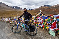 A bicyclist stops at the summit of 16,000 foot Bara-lacha Pass, Leh-Manali Highway, Himachal Pradesh, India.