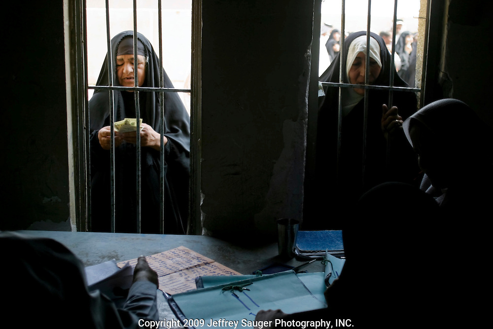 An Iraqi woman, left, counts her $40/month social security payment as other wait for theirs in Nasiriyah, Iraq, Tuesday, August 12, 2003. The director of the program said he receives $2 million per month from the Coalition Provencial Authority and because of the number of people they provide for can only give out $40/month payments.