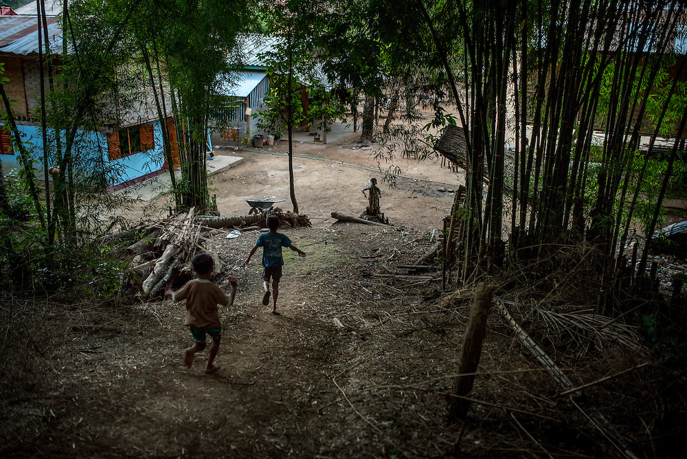 Children run through the bamboo forest that surround the village of Khoc Kham. The village is not connected to the main electrical grid and many residents operate their own turbines to power lights and sometimes small appliances.