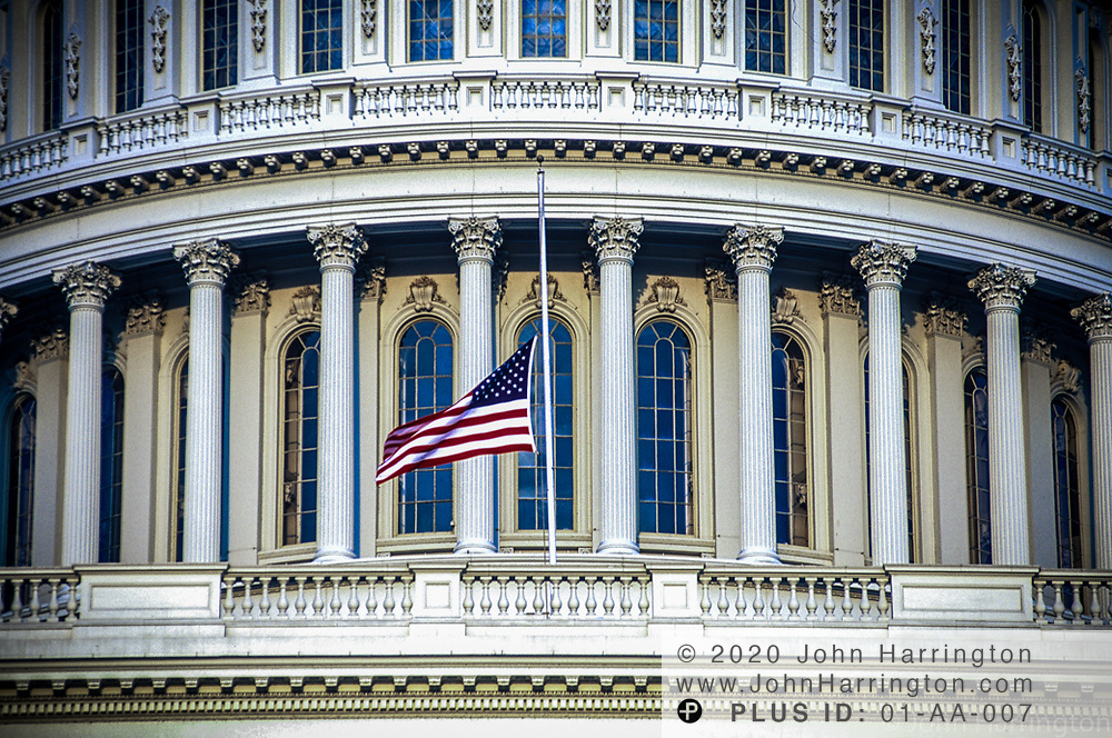 The US Capitol with the flag at half mast.