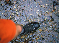 Detail view looking down at the boot of a man hiker crossing a shallow stream<br />