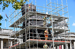 © Licensed to London News Pictures. 29/07/2020. LONDON, UK.  Construction workers remove scaffolding around artist Heather Phillipson's 'THE END', which will soon be unveiled to the public as the new Fourth Plinth artwork in Trafalgar Square.  THE END will show a giant swirl of replica whipped cream topped with a cherry, a fly and a drone.  Its drone will transmit a live feed of the square which can be watched on a dedicated website.  The installation, originally planned for 26 March 2020, but postponed due to the coronavirus pandemic will remain on display for the next year two years.  Photo credit: Stephen Chung/LNP