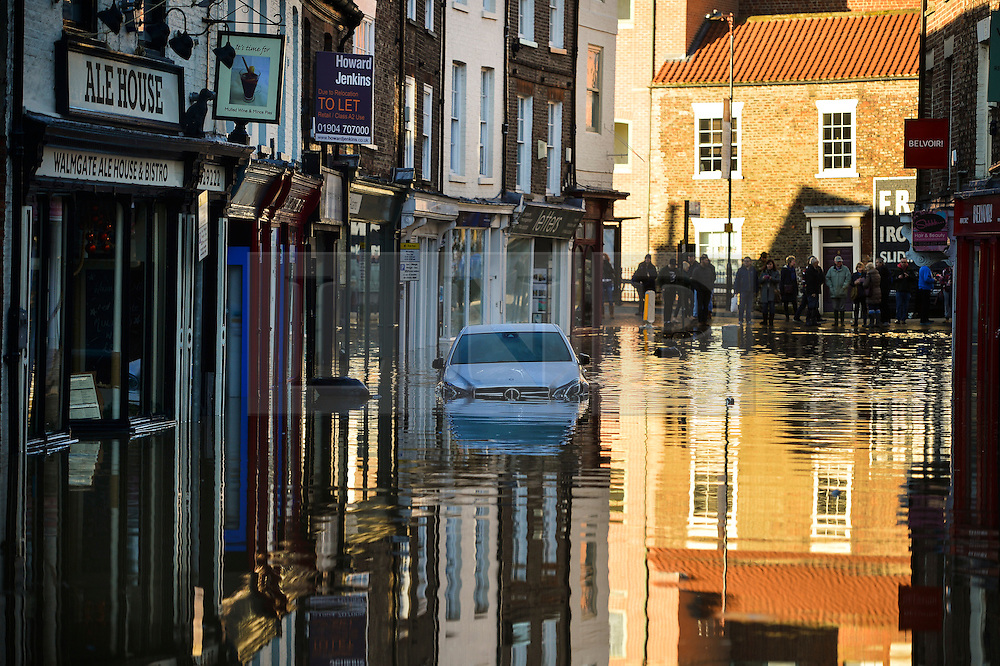 © Licensed to London News Pictures. 27/12/2015. York, UK.  A car sat in deep flood water in the city Centre of York following heavy flooding. Large areas of the North of England have been hit by severe flooding following unusually heavy rainfall in December. Photo credit: Ben Cawthra/LNP