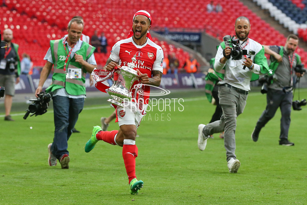 Arsenal's Theo Walcott(14) runs with the FA CUP during the The FA Cup final match between Arsenal and Chelsea at Wembley Stadium, London, England on 27 May 2017. Photo by Shane Healey.