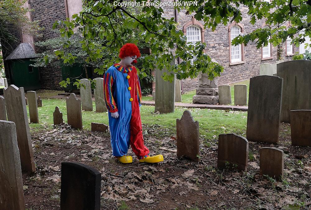 A clown walks through a cemetery in New Brunswick, NJ, Sept. 24 2006.