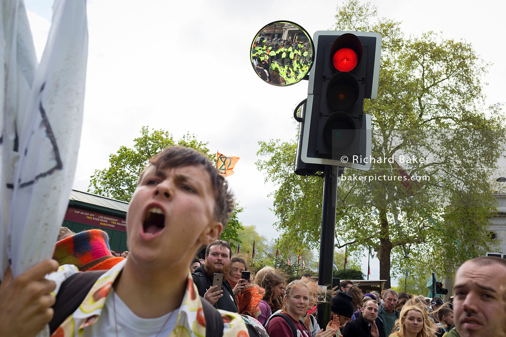 On the 10th consecutive day of protests around London by the climate change campaign Extinction Rebellion, activists shout beneath a traffic mirror filled withe police officers who are preparing to make arrests, on 24th April 2019, at Marble Arch, London England.