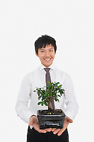 Portrait of happy mid adult businessman holding potted plant over white background