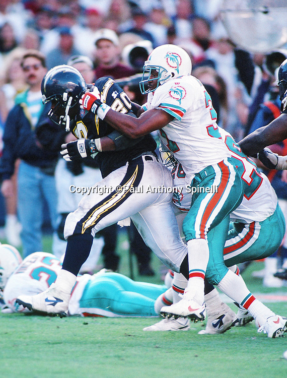 San Diego Chargers running back Natrone Means (20) gets tackled from behind as he runs the ball during the NFL AFC Divisional playoff football game against the Miami Dolphins on Jan. 8, 1995, in San Diego. The Chargers won the game 22-21. (©Paul Anthony Spinelli)