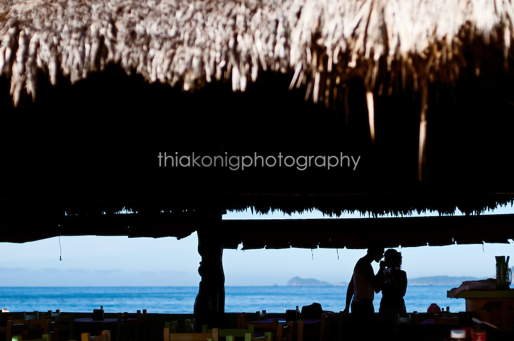 Silloette of couple sharing a drink through straws with thatched roof, ocean view in the background, Barra de Navidad, Mexico.