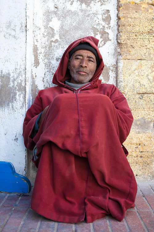 A muslim man, wearing a traditional red djellaba, in the old medina of Essaouira, Morocco.