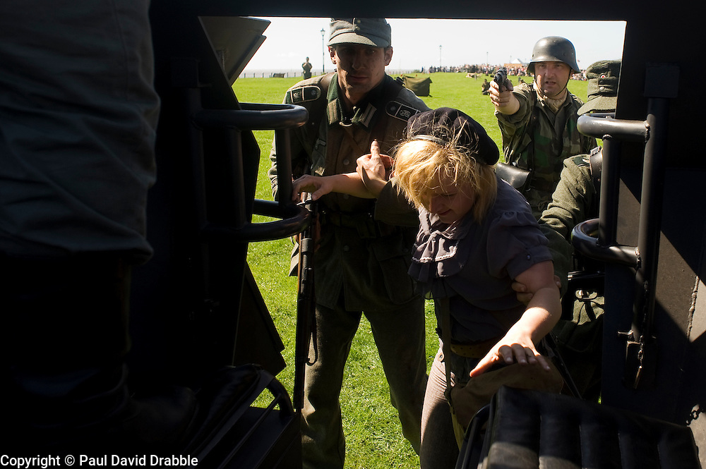 A reenactors portray  German Panzergrenadiers (GrossDeutschland Regiment)  taking a female partisan prisoner during a battle re-anactment at the The first Annual Lytham 1940s Weekend held to celebrate the 70th anniversary of the battle of Britain and raise funds for a new Fighter and Bomber Command Memorial to be erected in Lytham. 21 August 2010 Images © Paul David Drabble..