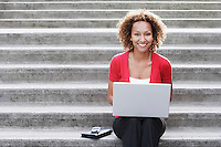 Woman using laptop on steps portrait