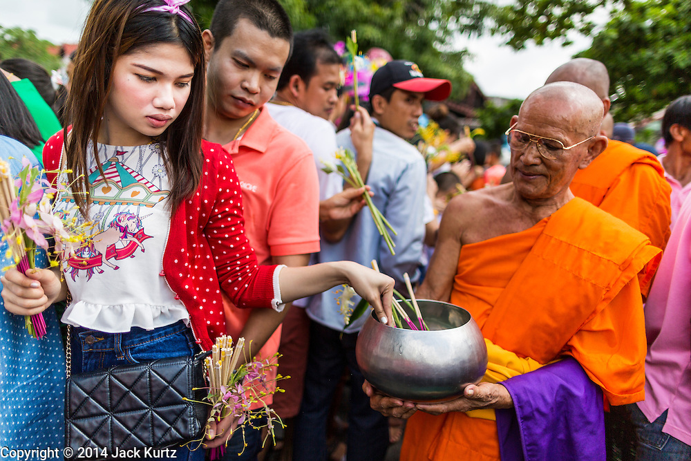 "12 JULY 2014 - PHRA PHUTTHABAT, SARABURI, THAILAND:  A woman puts flowers into a monk's bowl during the Tak Bat Dok Mai at Wat Phra Phutthabat in Saraburi province of Thailand. Wat Phra Phutthabat is famous for the way it marks the beginning of Vassa, the three-month annual retreat observed by Theravada monks and nuns. The temple is highly revered in Thailand because it houses a footstep of the Buddha. On the first day of Vassa (or Buddhist Lent) people come to the temple to ""make merit"" and present the monks there with dancing lady ginger flowers, which only bloom in the weeks leading up Vassa. They also present monks with candles and wash their feet. During Vassa, monks and nuns remain inside monasteries and temple grounds, devoting their time to intensive meditation and study. Laypeople support the monks by bringing food, candles and other offerings to temples. Laypeople also often observe Vassa by giving up something, such as smoking or eating meat. For this reason, westerners sometimes call Vassa ""Buddhist Lent.""   PHOTO BY JACK KURTZ"