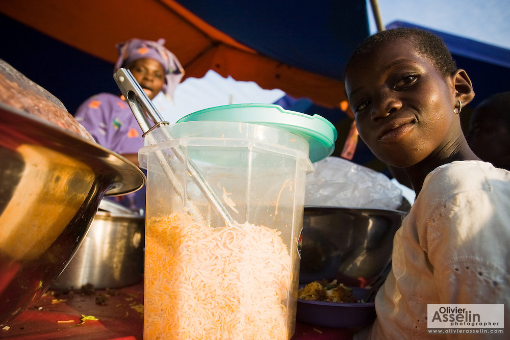 A young girl waits for her order to be ready at a small kiosk selling food during the annual Oguaa Fetu Afahye Festival in Cape Coast, Ghana on Saturday September 6, 2008.