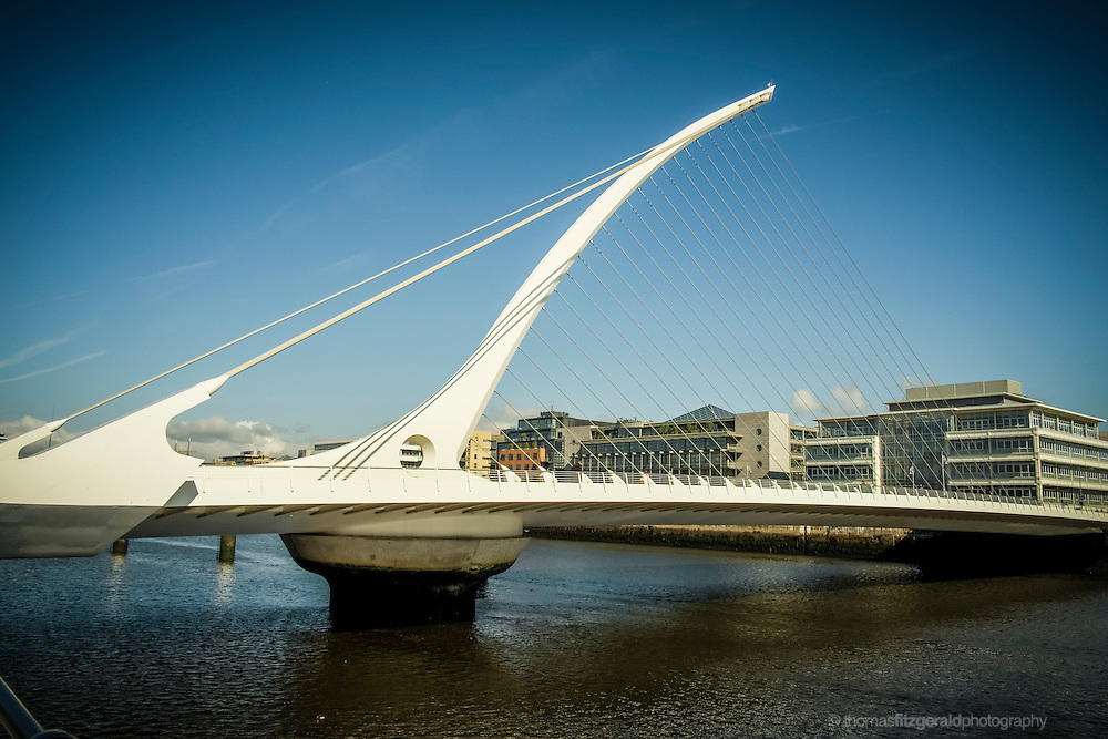 An image of the iconic Samuel Beckett bridge in Dublin City, which stretches over the river Liffey with its majestic hart shaped suspension cables.
