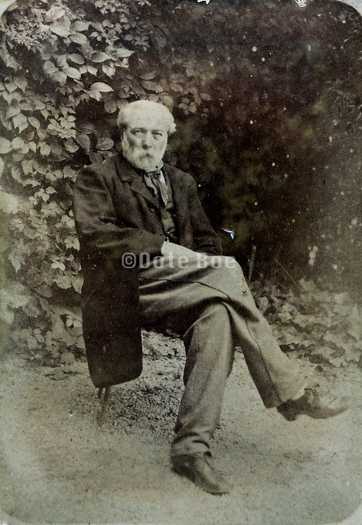 vintage portrait of an adult man sitting on a chair in garden setting