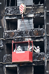 August 16, 2017 - London, London, UK - London, UK. Workmen in a crane outside the Grenfell residential tower block in West London are seen wrapping the tower with a cling film type material. The tower was engulfed by a fire two months ago causing at least 80 deaths and over 70 injuries. Up to 200 survivors are still living in hotels and have resorted to searching for new homes themselves out of frustration at the council's rehousing efforts. (Credit Image: © Ray Tang/London News Pictures via ZUMA Wire)