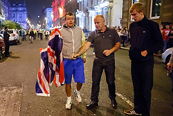© Licensed to London News Pictures. 19/09/2014. Glasgow, UK. Scottish independence supporters attempting to burn a union jack whilst posing against pro-unionists and at George Square in Glasgow as Scotland decides to stay in the union and First Minister Alex Salmond resigns over the results of the Scottish independence referendum on Friday, 19 September 2014. Photo credit : Tolga Akmen/LNP