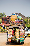09 MARCH 2013 - ALONG HIGHWAY 13, LAOS:  An overloaded songthaew (pickup truck converted to bus) on Highway 13 in the province of Vientiane in Laos. The paving of Highway 13 from Vientiane to near the Chinese border has changed the way of life in rural Laos. Villagers near Luang Prabang used to have to take unreliable boats that took three hours round trip to get from the homes to the tourist center of Luang Prabang, now they take a 40 minute round trip bus ride. North of Luang Prabang, paving the highway has been an opportunity for China to use Laos as a transshipping point. Chinese merchandise now goes through Laos to Thailand where it's put on Thai trains and taken to the deep water port east of Bangkok. The Chinese have also expanded their economic empire into Laos. Chinese hotels and businesses are common in northern Laos and in some cities, like Oudomxay, are now up to 40% percent. As the roads are paved, more people move away from their traditional homes in the mountains of Laos and crowd the side of the road living off tourists' and truck drivers.    PHOTO BY JACK KURTZ