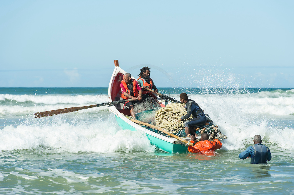 Trek-Net fishers pushing their boat out through the waves, Strandfontein, False Bay, Western Cape, South Africa