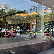 A steet scene with window reflections in Ho Chi Minh City, Vietnam. 3rd March 2012. Photo Tim Clayton