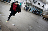 SYRIA - Al Qsair. Running away from Syrian Army snipers in Al Qsair, on January 24, 2012. Al Qsair is a small town of 40000 inhabitants, located 25Km south-west of Homs. The town is besieged since the beginning of November and so far it counts 65 dead. ALESSIO ROMENZI