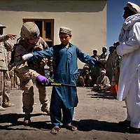 Spc. Brett Hamilton uses a metal detector on a young boy waiting to enter the medical clinic near Forward Operating Base Salerno in Afghanistan. fom Afghanistan