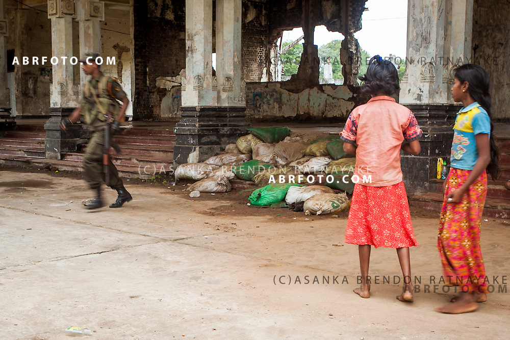 Army officer runs out of the abandoned Jaffna railway station as two homeless girls whom live within the railways staion look on.