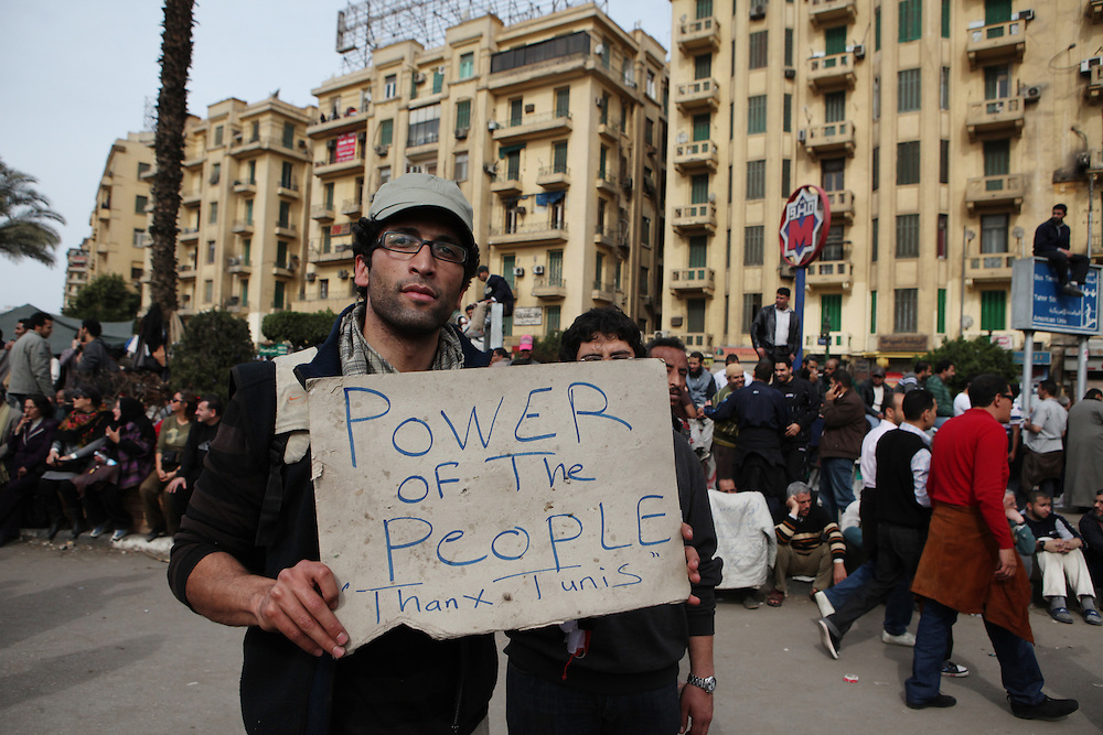 A protester at Tahrir Square holds a sign thanking Tunisians who overthrew their government last month.