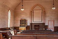 """Inside the old Methodist church at Bodie State Historic Park. At the front of the room a quotation reads, """"Praise waiteth for thee o god in Zion."""""""