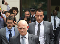 © London News Pictures. 13/07/2012. London, UK. England Footballer and Chelsea FC Captain JOHN TERRY (right) leaving Westminster Magistrates court, escorted by security on July 13, 2012, where a verdict  of not guilty was returned  today in John Terry's trial for allegedly using a racist obscenity about Queens Park Rangers player Anton Ferdinand. Photo credit: Ben Cawthra/LNP.