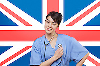 Portrait of mixed race female surgeon standing over British flag