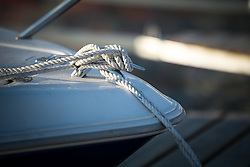 Rope tied at the front of a motorboat.