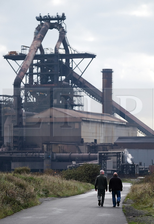 © Licensed to London News Pictures.20/10/15<br /> Redcar, UK. <br /> <br /> Two men walk along the road in front of the recently closed SSI UK steel blast furnace in Redcar, England. The closure of the site marks the end of 170 years of steel making heritage on Teesside and was the first of a number of recent closures of steel making plants across the UK.<br /> <br /> Photo credit : Ian Forsyth/LNP