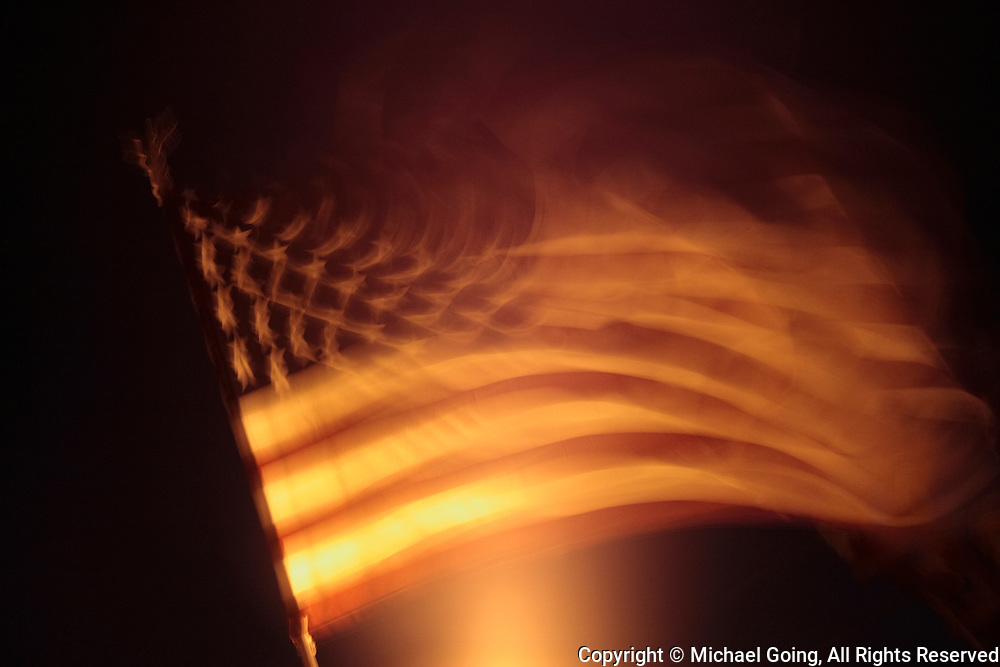 Motion blur of American Flag at night with back lighting