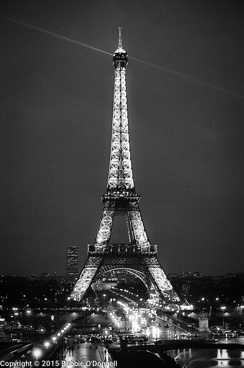 The Eiffel Tower, an iconic landmark shines brightly against a night sky. Beams of light illuminate the Eiffel Tower from the inside of its structure, as it's beacon shines over the city.